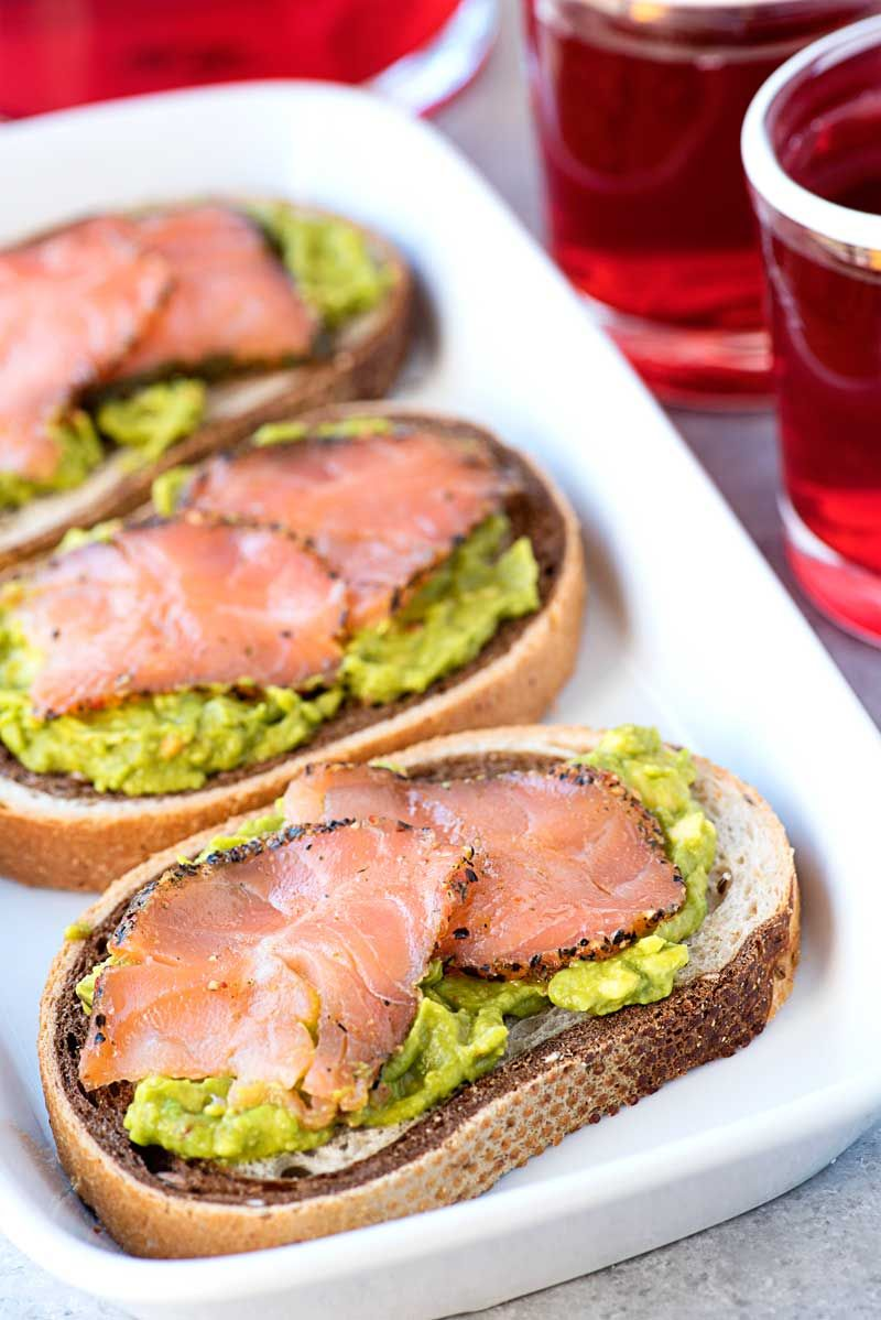 A savory smoked salmon appetizer with chili avocado spread on rye bread and served with Tazo ® Passion Tea that you can #SipJoyfully.
