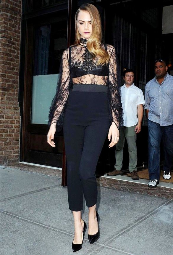 Cara Delevingne wears a lace high-neck top, black bra, high-waisted black trousers, and pumps
