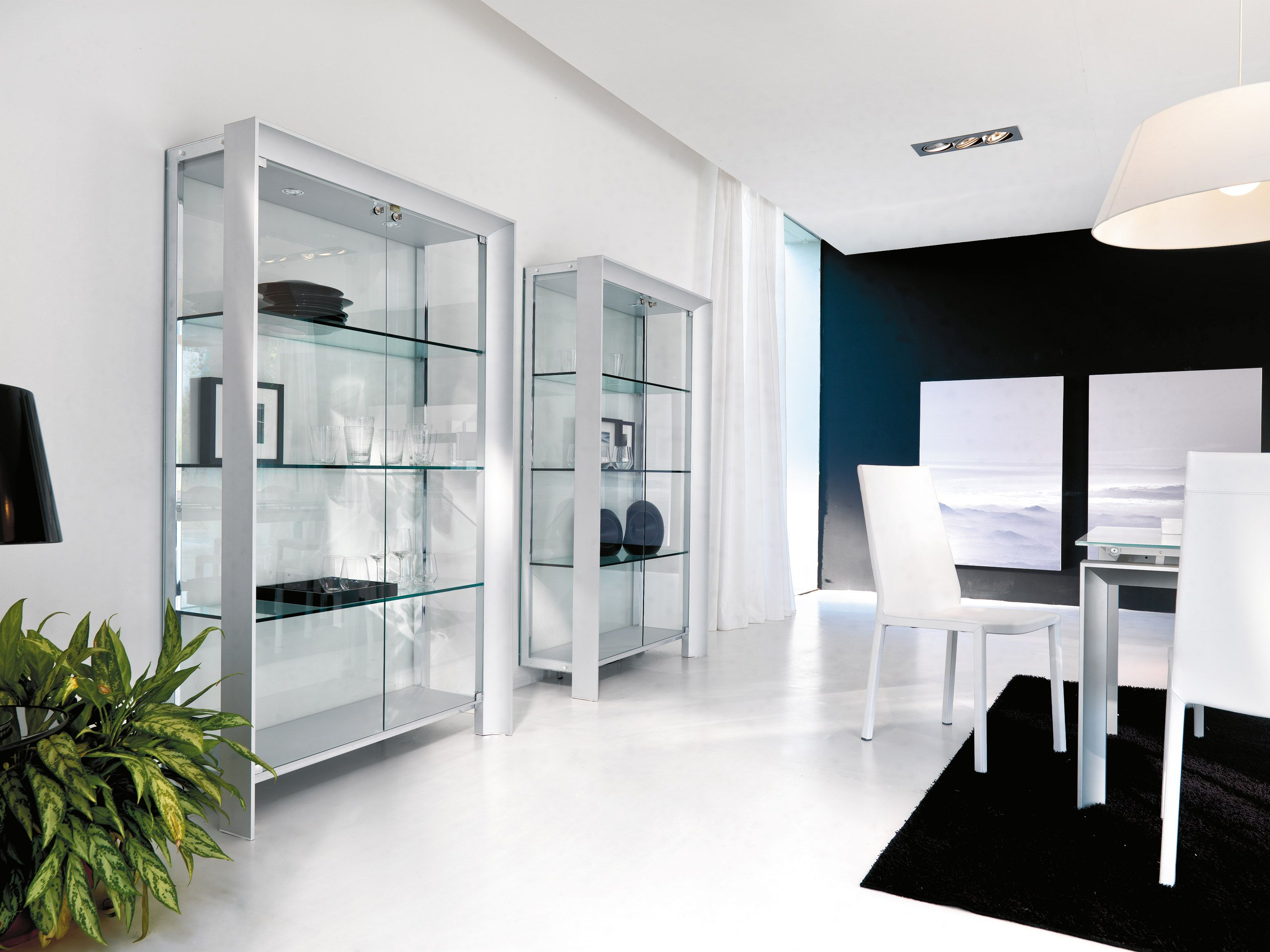 Aurora glass cabinet with sides, back panel and shelves in tempered glass and supporting structure wood veneered in different finishing. Aurora is a simple glass cabinet that easily adapts into any ambient in your home. Available also with internal led light spot.