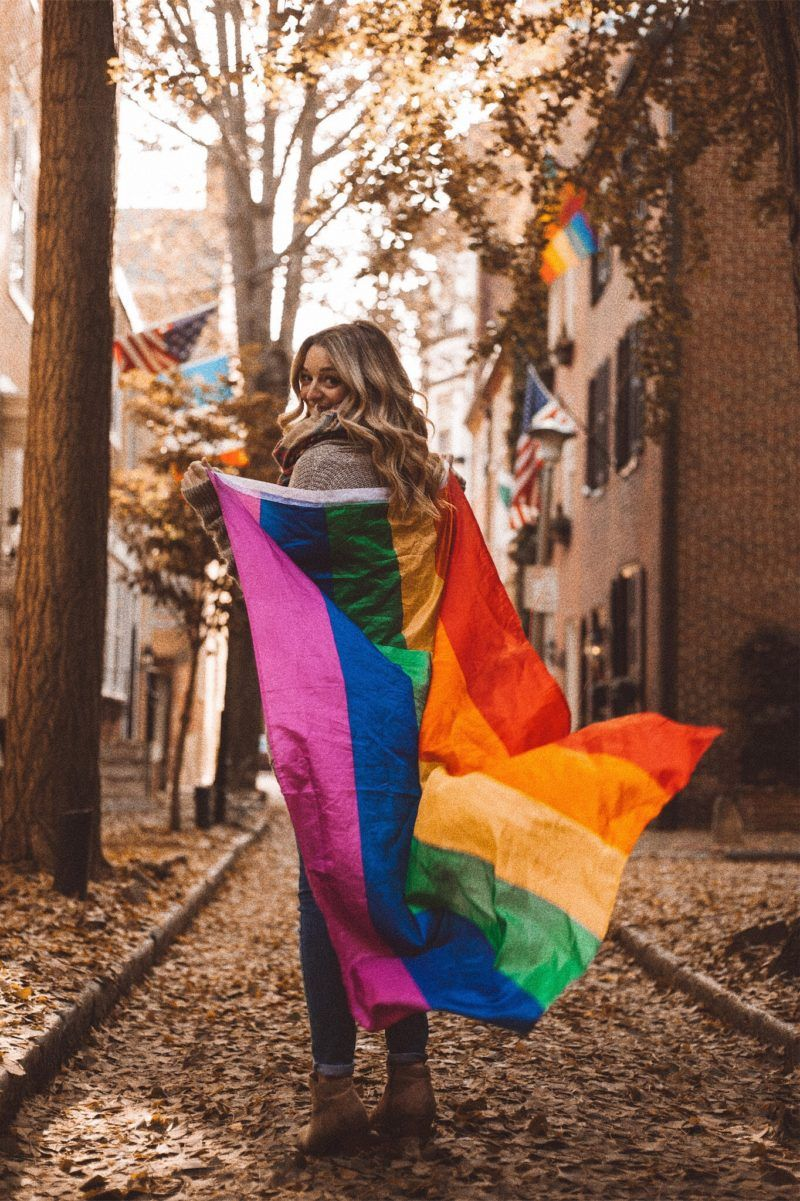 Kate austin walking down the street with a rainbow pride