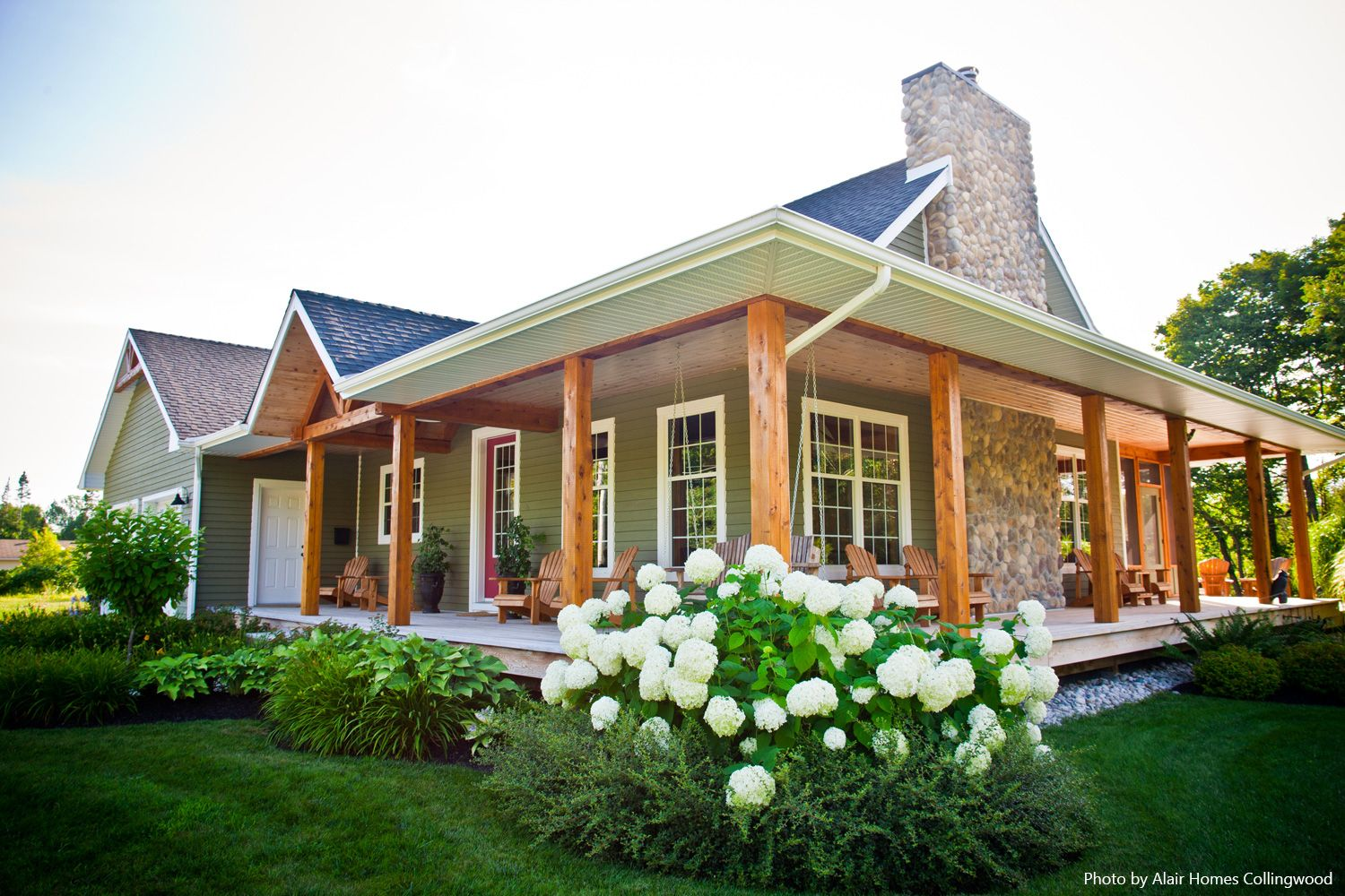 Breathtaking! What beauty this home has to offer, from a stone covered chimney to a red entry door, and a southern style porch, the exterior sure does shine. If you're thinking about building your own deck, click the pin to see our tips and advice for this type of project.