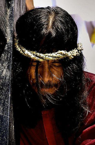 Settimana santa, Pampanga, Filippine.  Un uomo che rimette in vigore la sofferenza di Gesù, portando una croce per le strade.  Il culmine della quale viene inchiodato sulla croce di fronte a migliaia di persone.