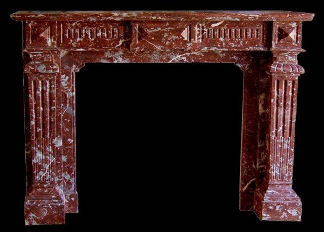 Exceptional carved rouge marble fire mantel with fluted side columns and decorative details.