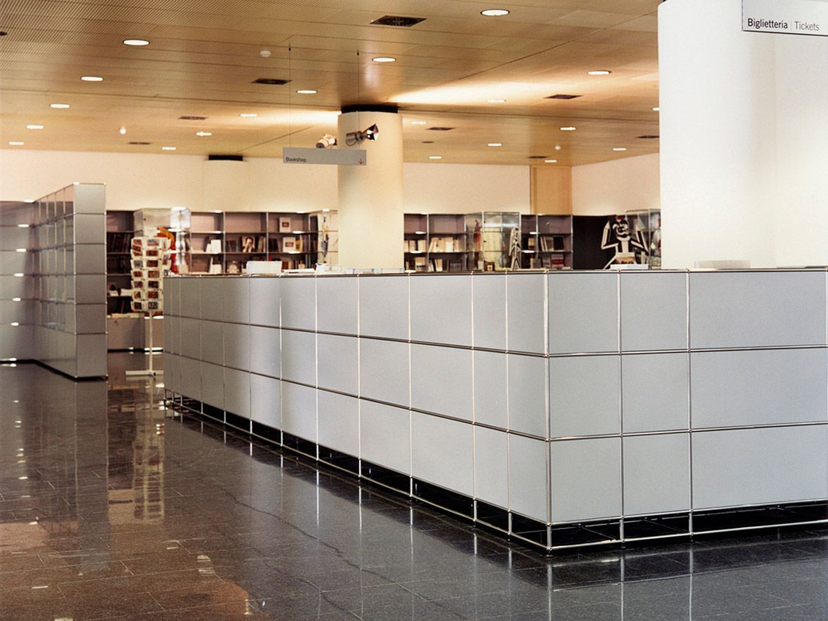 A pure white USM Haller reception station and light grey shelvings ...