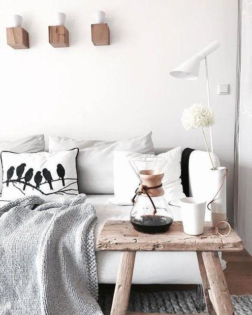 Das Weiß Des Sofas Bringt Dieses Wohnzimmer Zum Strahlen. Der Hocker Aus  Natürlichem Holz Und Die Grauen Farbakzente Sorgen Für Ein Gemütliches  Ambiente.