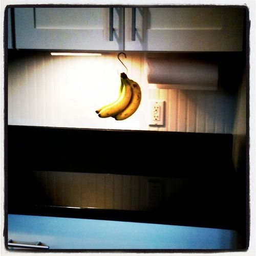 """Use a cup hook and an """"s"""" hook to hang bananas under the cabinet. When not in use just hide the """"s"""" hook. This is such a great space saver!"""