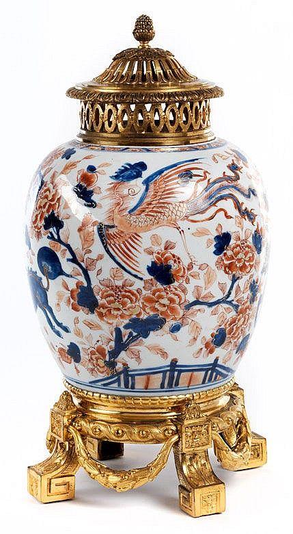 Brûle parfum, Höhe: 43 cm.  <br /> 18./ 19. Jahrhundert.  <br />  <br /> Japanische Kakiemon-Vase aus Porzellan, montiert in einen vierfüßigen Unterbau mit Blattkranzgirlanden. Der Deckel ringsum mit ovalen Öffnungen, durchbrochen gearbeitet. Der Deckel ähnlich, als Abschluss nach oben ein Pinienzapfen. (8812111)