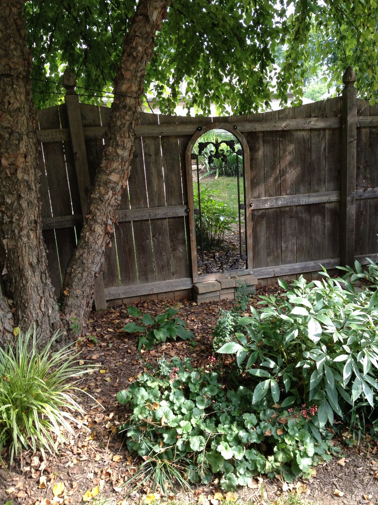 Attached A Mirror To The Garden Fence Gives The Appearance Of An