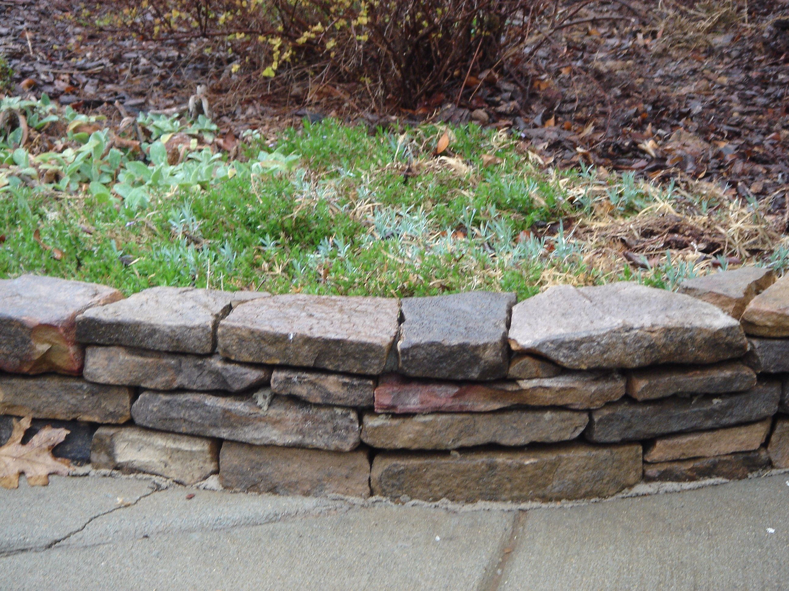 stacked stone flower bed border front yard curb appeal