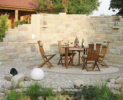 Die Halbrunde Mauer Aus Betonstein Rahmt Den Sitzplatz Stimmungsvoll Ein.  Die Wechselnden Farbtöne Und Formate Der Steine Geben Ihr Einen Natürlichen.
