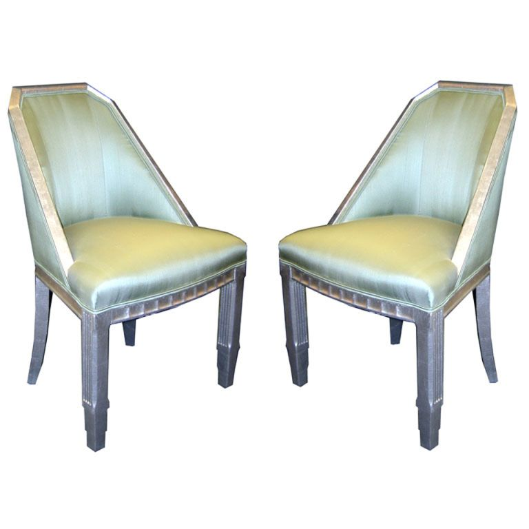 """This pair of French art deco occasional chairs date to the 1930's. Refinished in silver leaf and pale green Scalamandre silk, the chairs are suitable for any décor. The """"Telescope"""" front legs have vertical lines carved on the other sides and the front apron of the seat is carved in a series of geometric carthouches."""