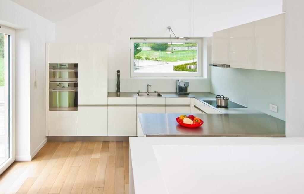 Minimalistische Küche weiß mit Edelstahl-Arbeitsplatte - küche fliesen ideen