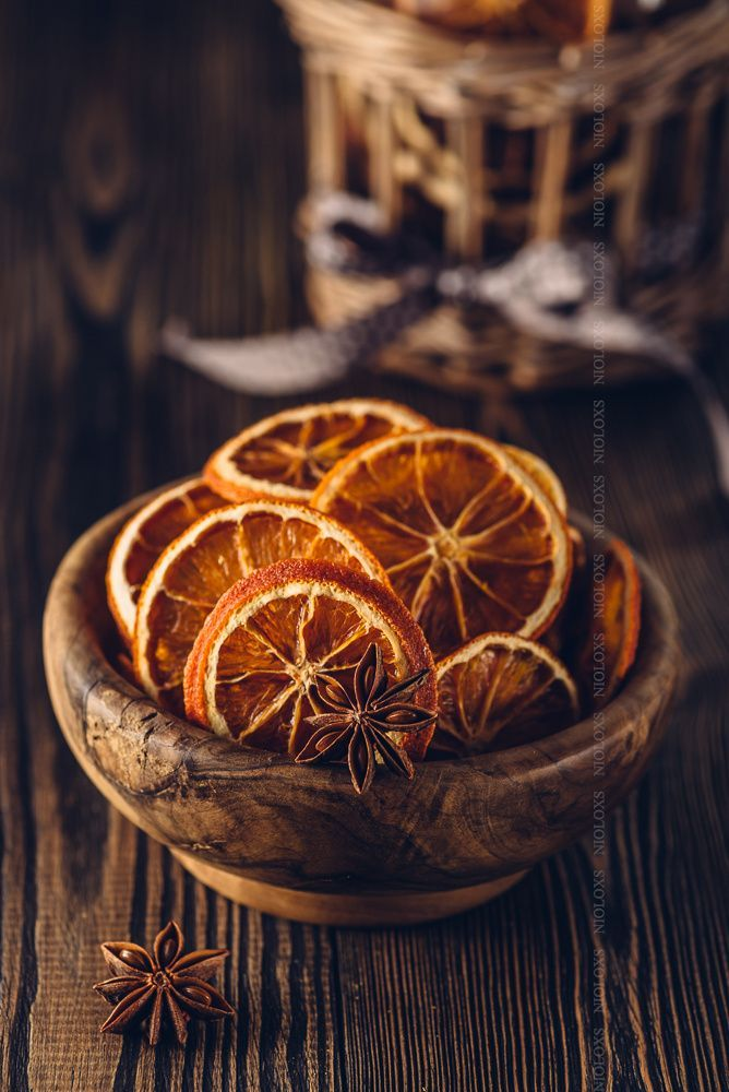 Anise and dried oranges in bowl on a wooden table.
