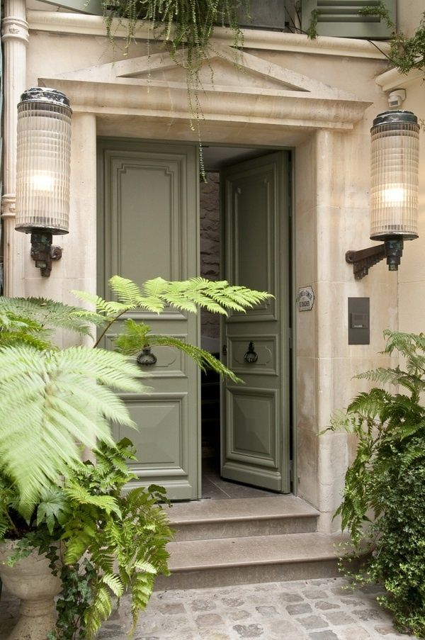 French Style Door In Unique Soft Green With Dark Hardware Against White Facade
