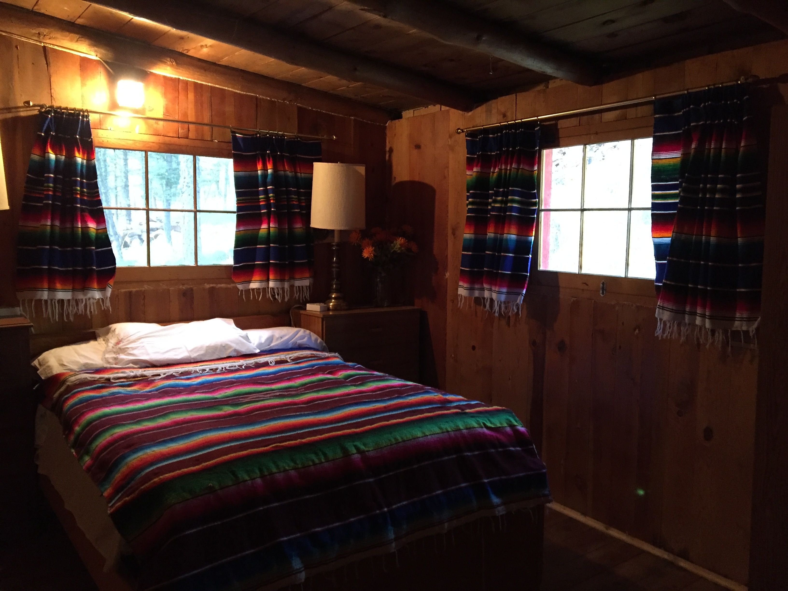 Here is a view with the curtains open. They are made from serape blankets. The rods are hung far to each side to accommodate the window when it is open. It opens up and there is a latch on the ceiling to hold the window open.