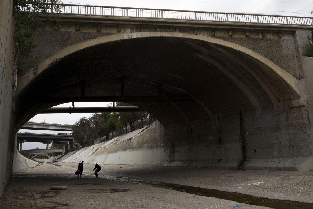 Two Homeless Men Walk Under A Bridge Along The Los Angeles