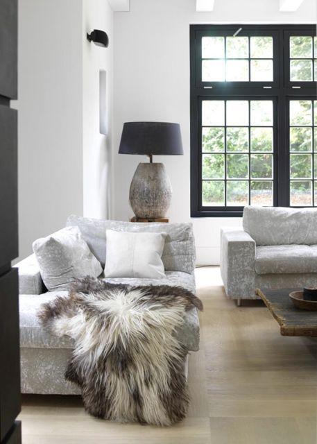 Woonkamer met veel licht, ruige meubelen en accessoires en een warm ...