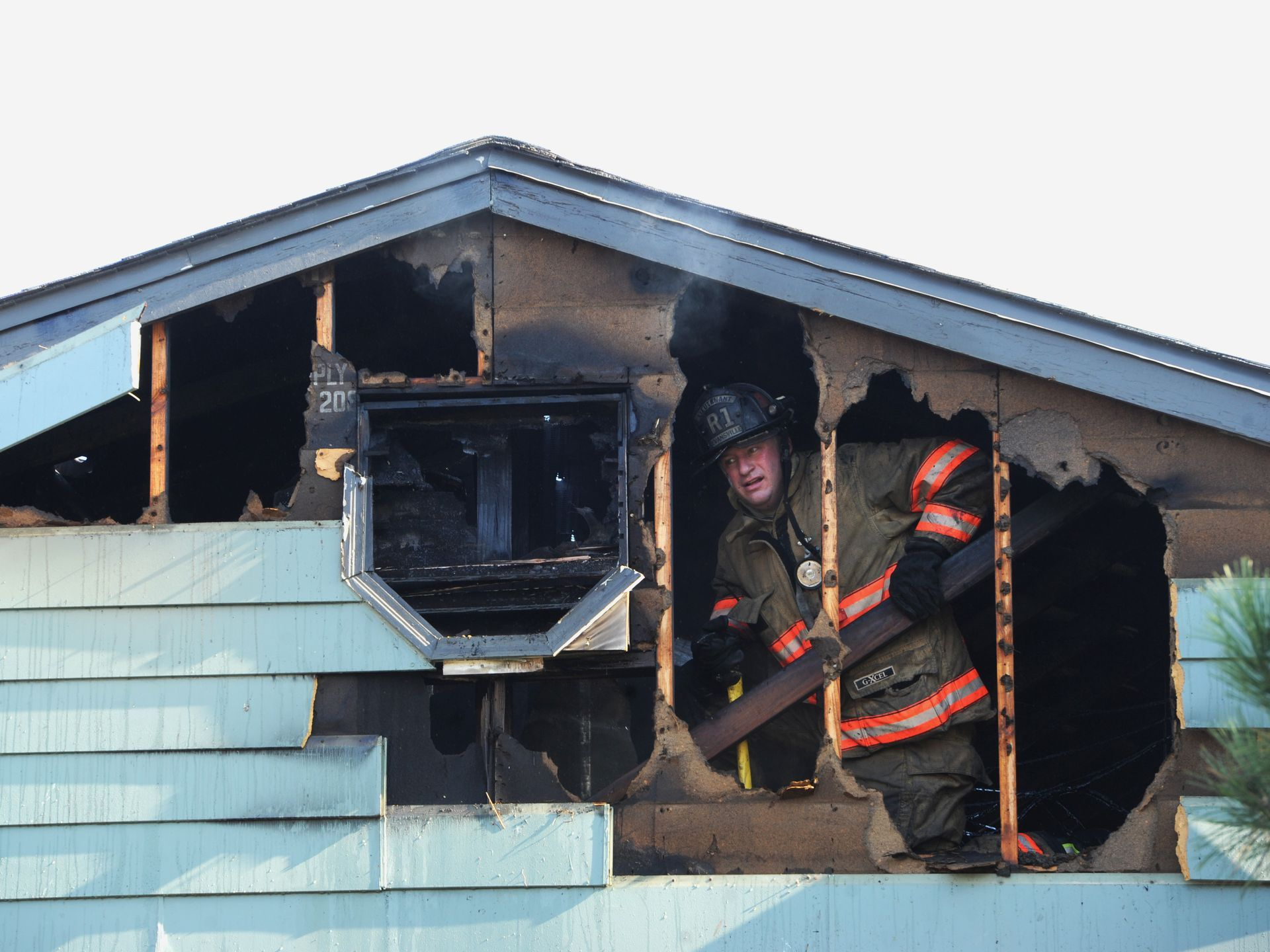 A firefighter works to vent the attic and roof of an apartment building in Evansville, Ind.   Erin McCracken, Evansville Courier & Press via AP