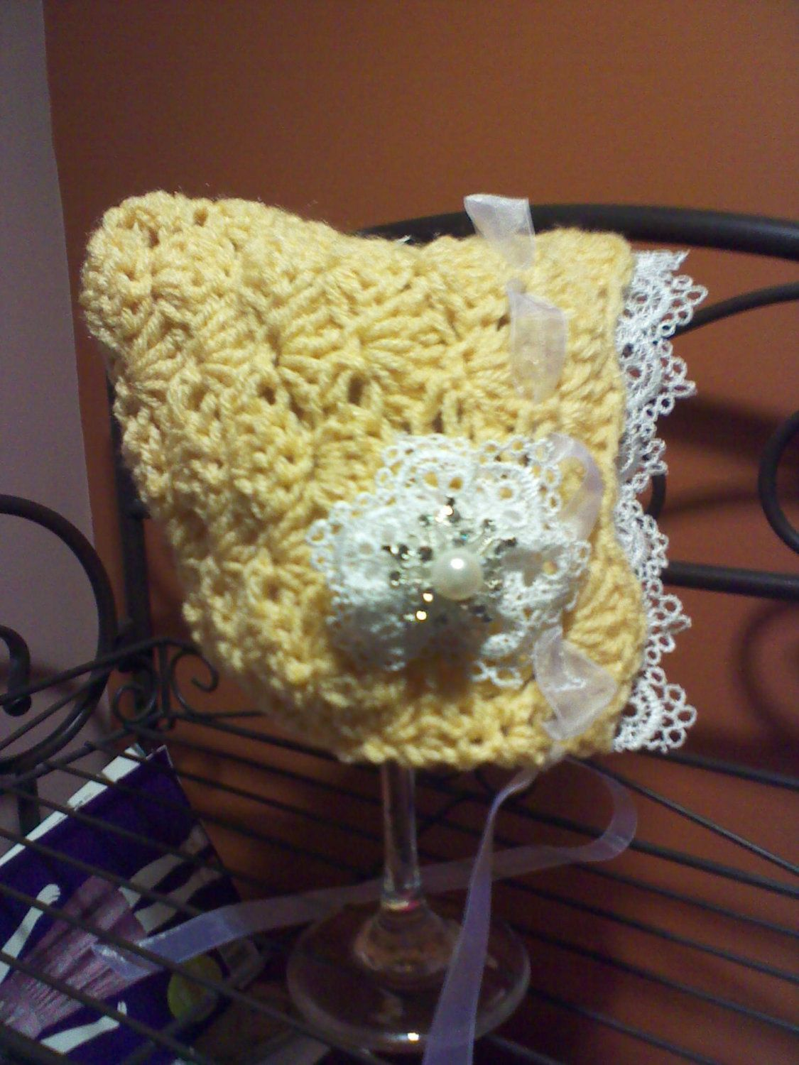 Yellow baby bonnet with lace flower. $12.00, via Etsy.