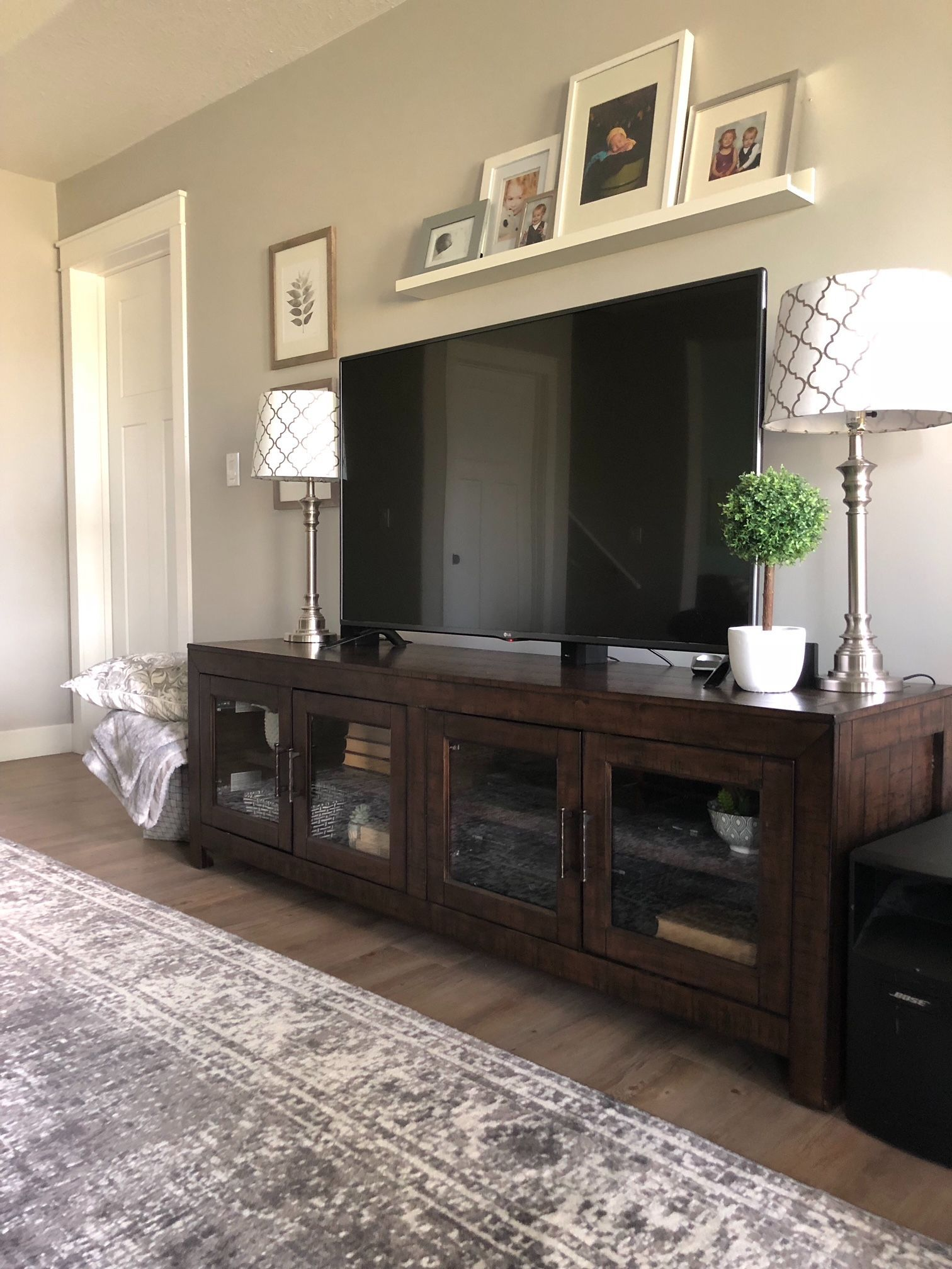 Tv Console With Glass Cabinet Doors In A Basement Media Room