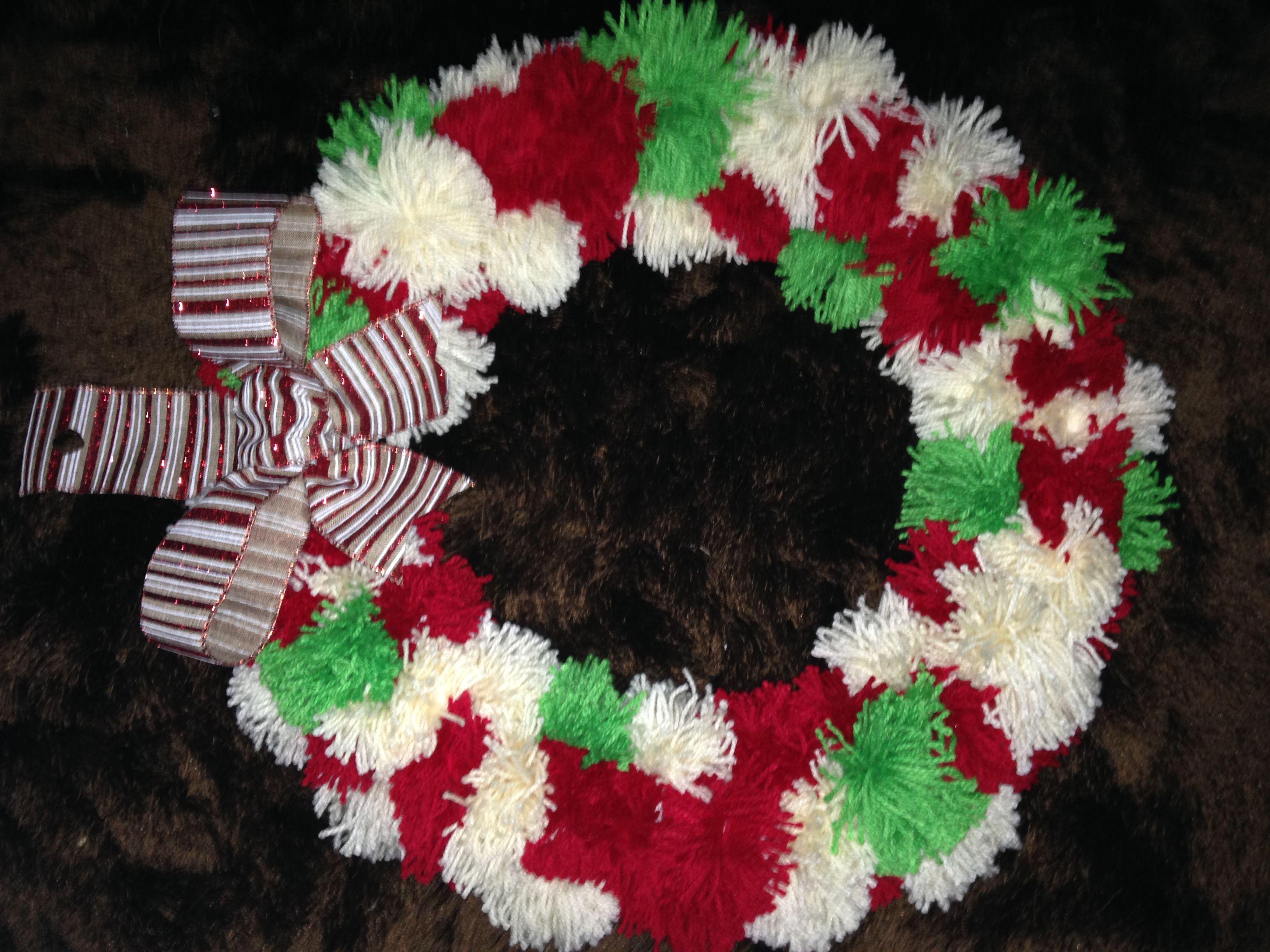 corona navidea hecha de pompones de estambre para la puerta de la casa