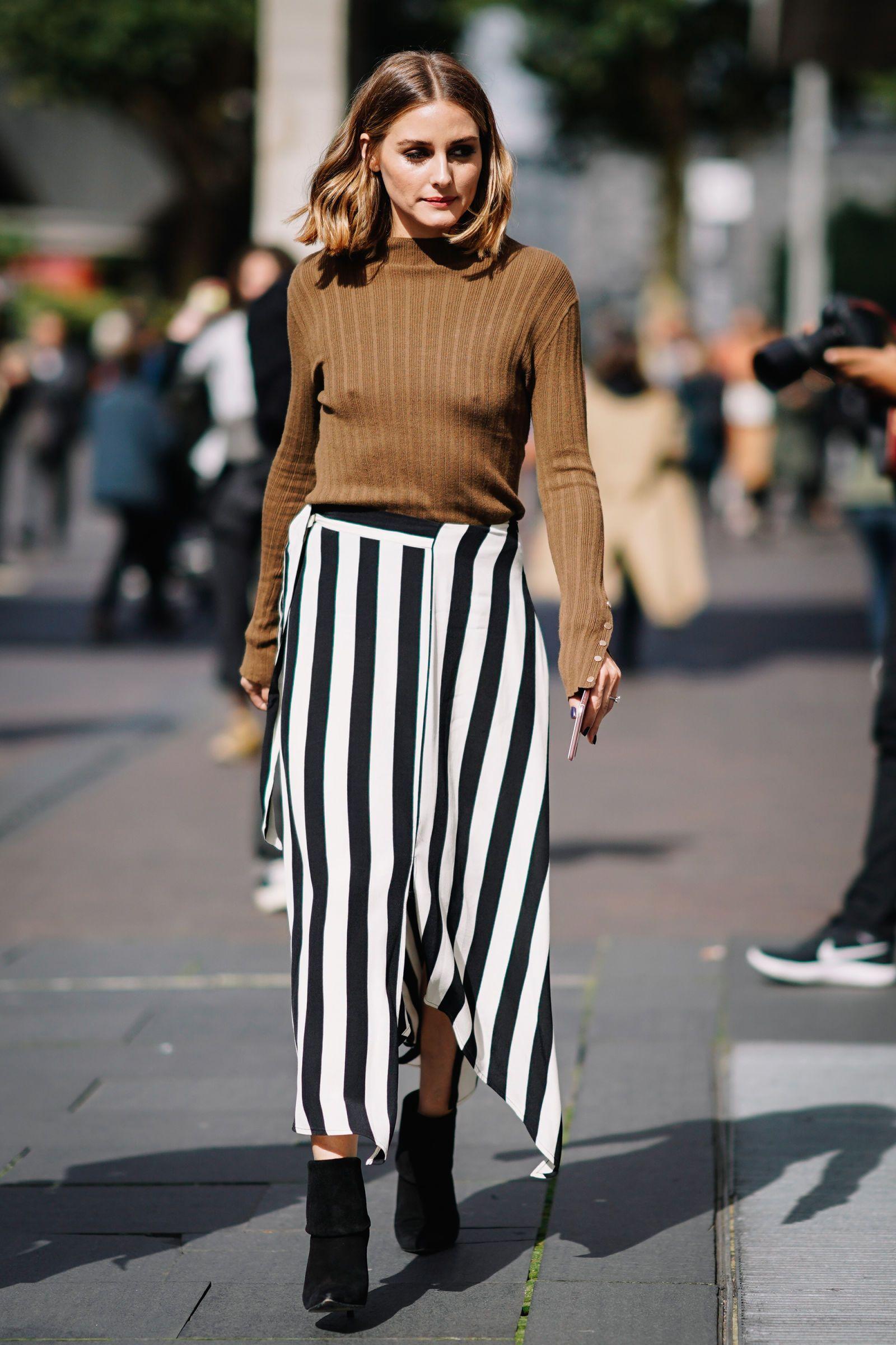 4ac5c4bb06d4 Olivia Palermo estrena cuatro looks en un mismo día. Falda asimétrica de  rayas con botas