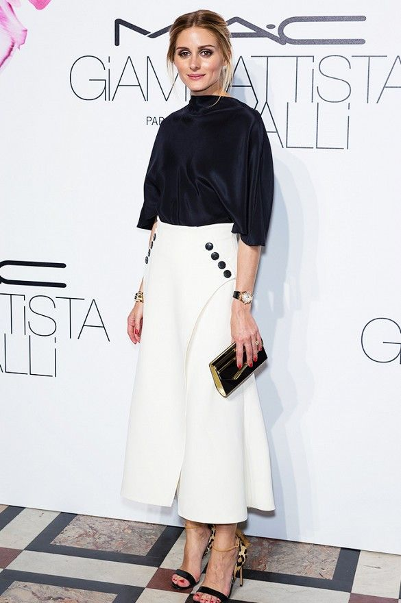 b3c5504bd37d Olivia Palermo wears a black top with a white skirt with button-detailing,  black and leopard sandals , and a metallic clutch