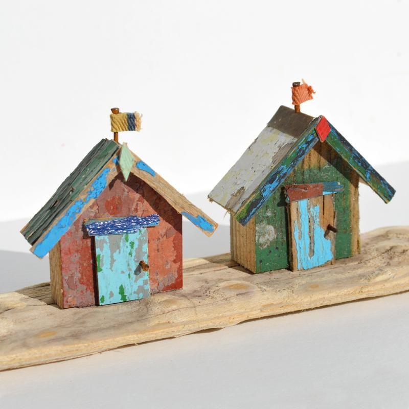 Driftwood art colourful beach huts on the beach