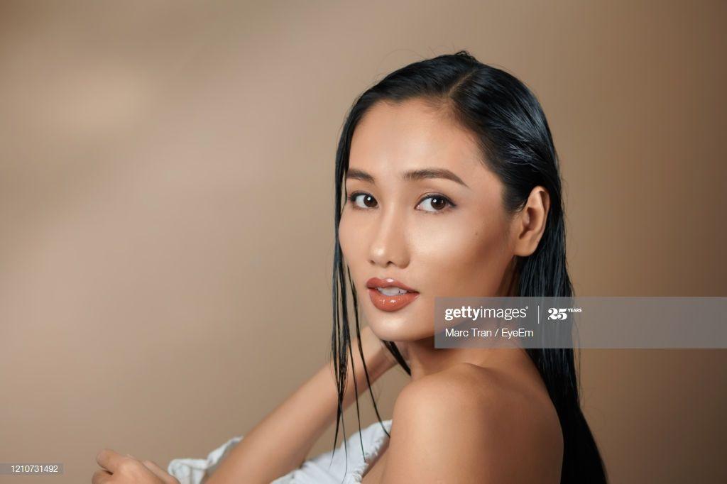 Closeup Portrait Of Beautiful Woman Looking Away Against Beige Background Photog #Ad, , #ad, #Beautiful, #Portrait, #Closeup, #Woman