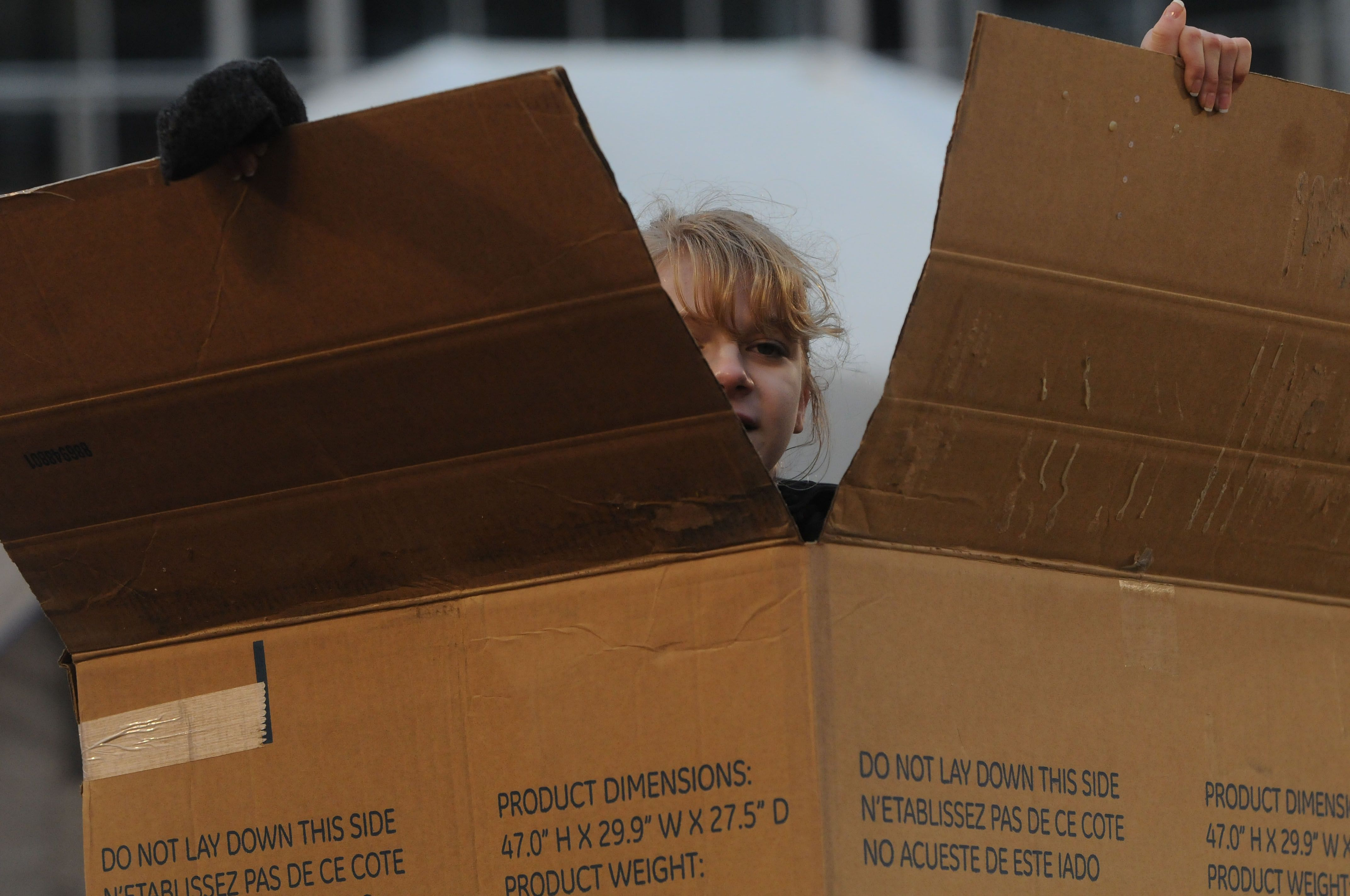 """Lara Murray, a member of Ames High SHEPH group, makes a shelter with cardboard boxes during the """"Reggie's Sleepout""""  event at Jack Trice Stadium Saturday, March 25, 2017, in Ames, Iowa. Photo by Nirmalendu Majumdar/Ames Tribune http://www.amestrib.com/news/20170325/community-braves-cold-rain-for-youth-homelessness-at-reggie8217s-sleepout"""