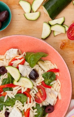 A colorful and original variation on traditional chicken salad, this dish combines chicken and vegetables — crisp zucchini, grape tomatoes, baby spinach leaves and roasted peppers — with Kalamata olives and orzo pasta. The subtle tartness of the lemon-infused olive oil dressing delicately brings all of the flavors together.