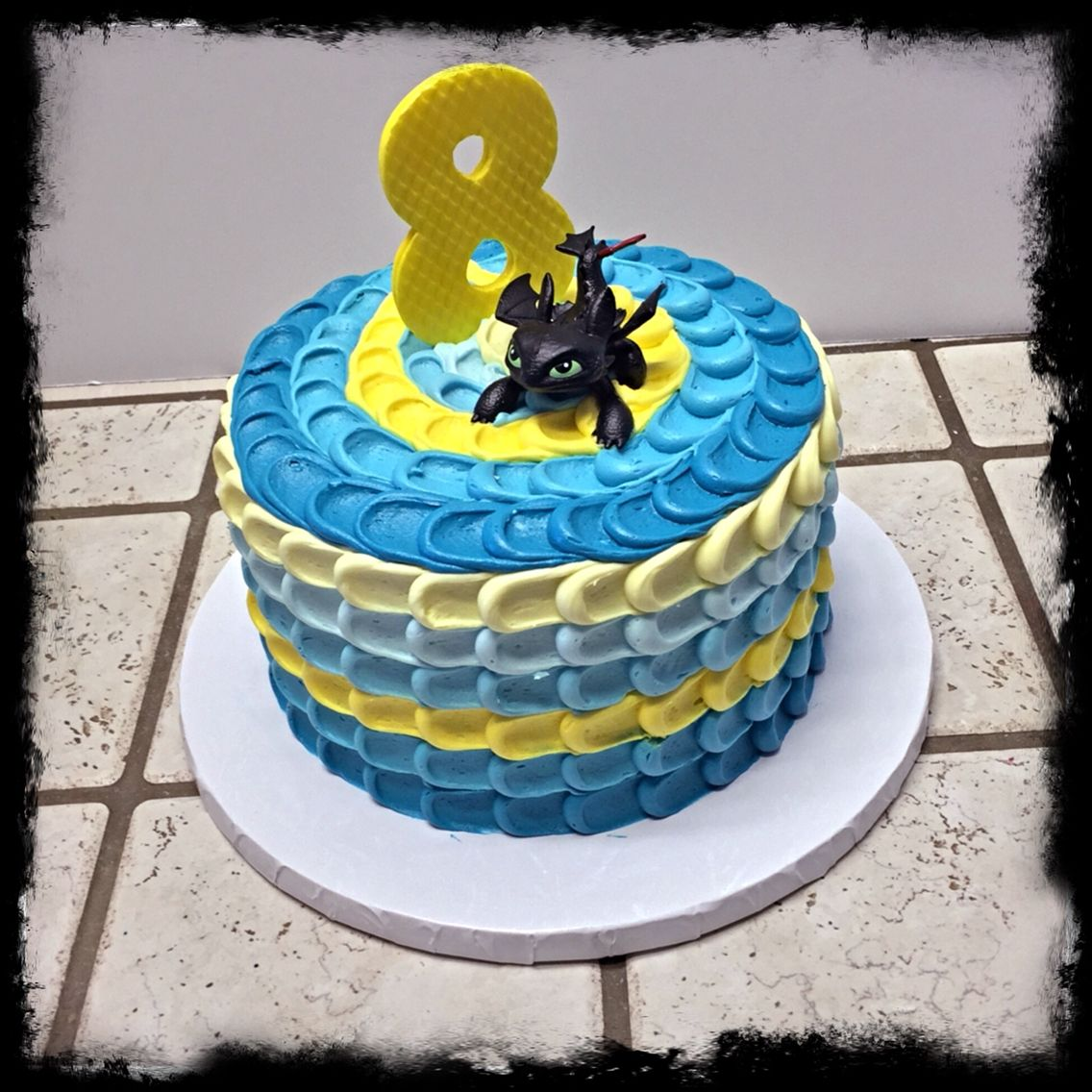 A Stormfly dragon colored cake with Toothless on top The Great