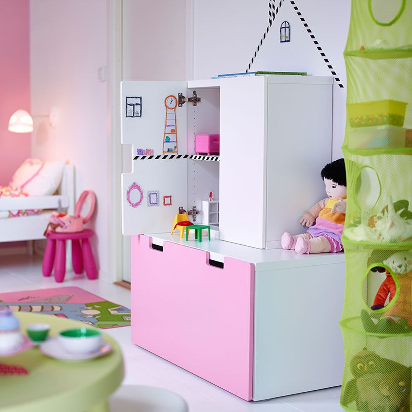 Doll's furniture inside a white cabinet on top of a white/pink storage bench