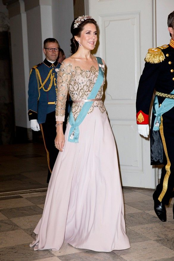 Denmark's Crown Princess Mary wears an off the shoulder sequin gown, shiny head crown, and earrings.