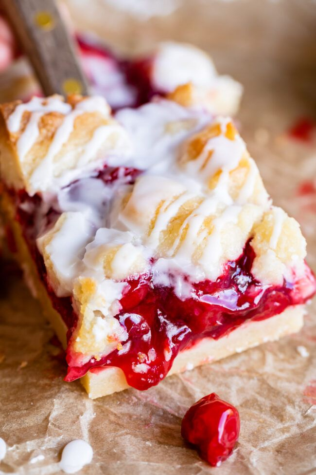 Easy Homemade Cherry Pie Bars from The Food Charlatan. These Cherry Pie Bars are a dream come true! A thick homemade shortbread crust, spread with cherry pie filling, then topped with thick pieces of more buttery shortbread! A vanilla glaze drizzled on top makes them irresistible. An easy way to serve pie when you're feeding a crowd! #pie #cherry #cherrypie #shortbread #bars #glaze #almond #easy #recipe #homemade #fromscratch #dessert #best #foracrowd #triedandtrue #sour #tart #cherrypiefilling