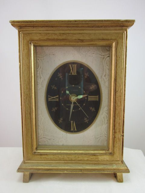 A gorgeous mid-century GE mantel clock with brushed gold casing and fleur-de-lis numerals.