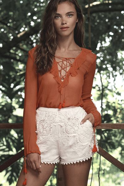 Romantic blouse in a stunning terracotta color way. long sleeves with tassel drawstring at cuff and a frilled v neckline with lace up tassel ties.