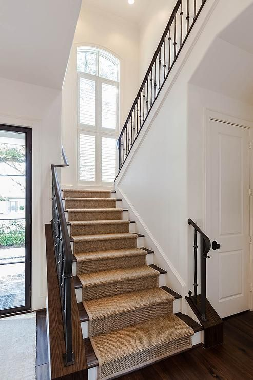 An Iron And Wood Staircase Is Lined With A Sisal Stair