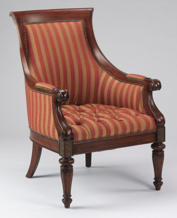 Empire Style armchair, with flared crestrail leading to scroll arms, the whole upholstered in nail-backed striped red and ochre fabric with a button-tufted seat, rising on turned front legs.