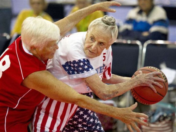 """Wearing the bun is 84-year-old Jane Soeten, the baby on the """"Sooner Gals,"""" Tulsa's team for women over 80. Link goes to a video of the Gals and three other Senior League women's teams having a clinic with the Tulsa Shock, in the run-up to the National Senior Games. [ @carlietwinkling found their names and the source - I struck out with nothing but crap links like """"FUNNY GRANNY BASKETBALL."""" Hrumph! It is clear from this shot that these are Real Women playing Serious Ball.]"""