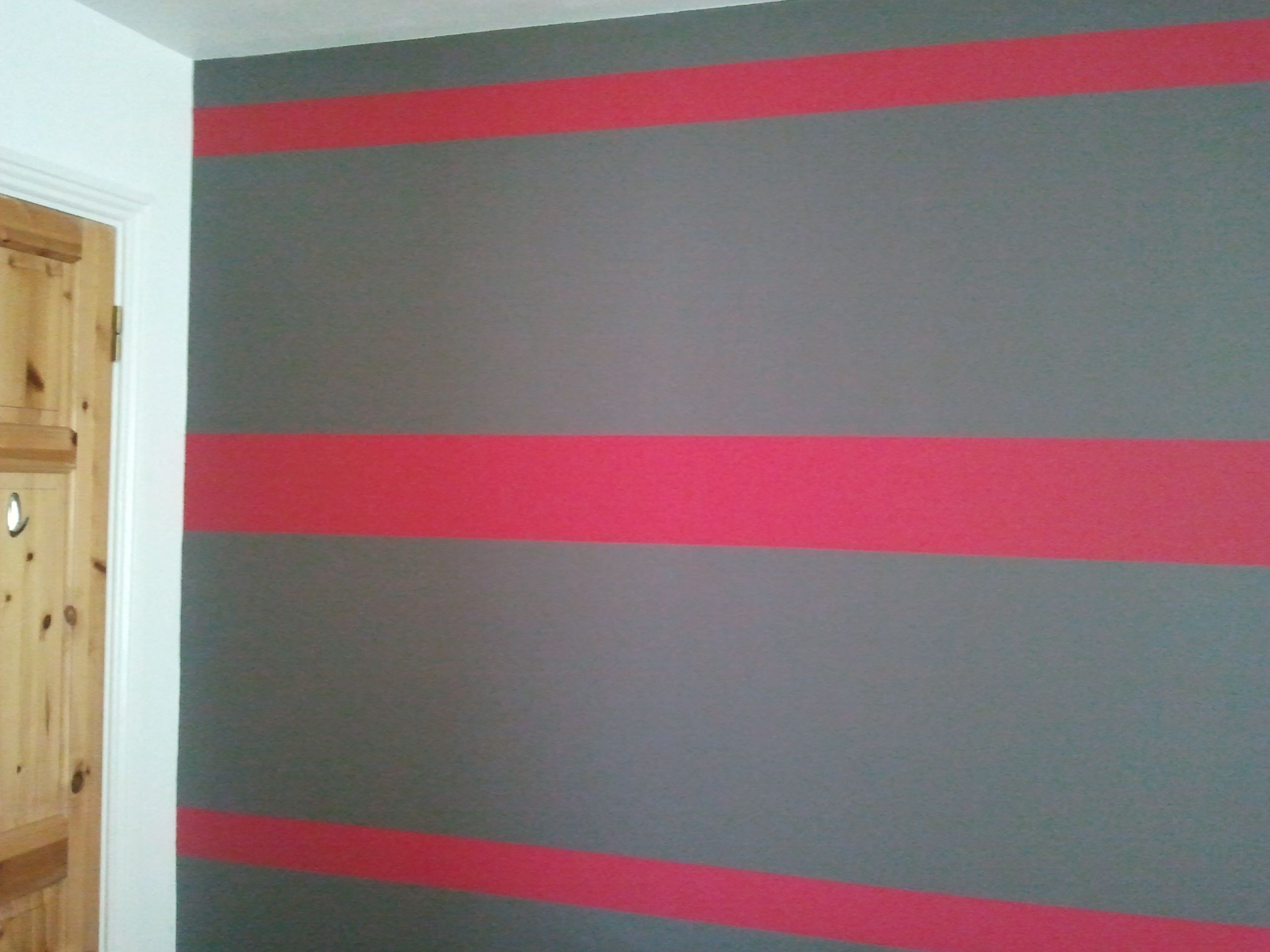 painted raspberry pink stripes on grey bedroom wall using masking