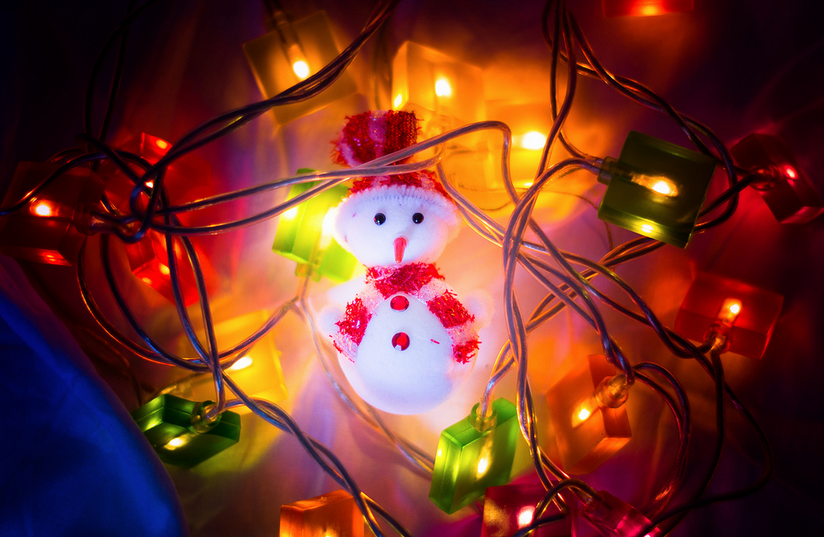 Christmas Snowman Is In A Garland On The Bed. The Lights Are On, So It Was  A Hot Feel For A Snowman!