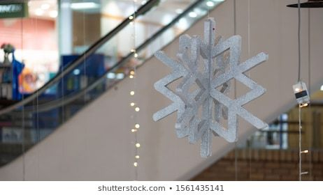 The symbol of snowflakes made of foam is hung in a mall next to the stairs in Thailand