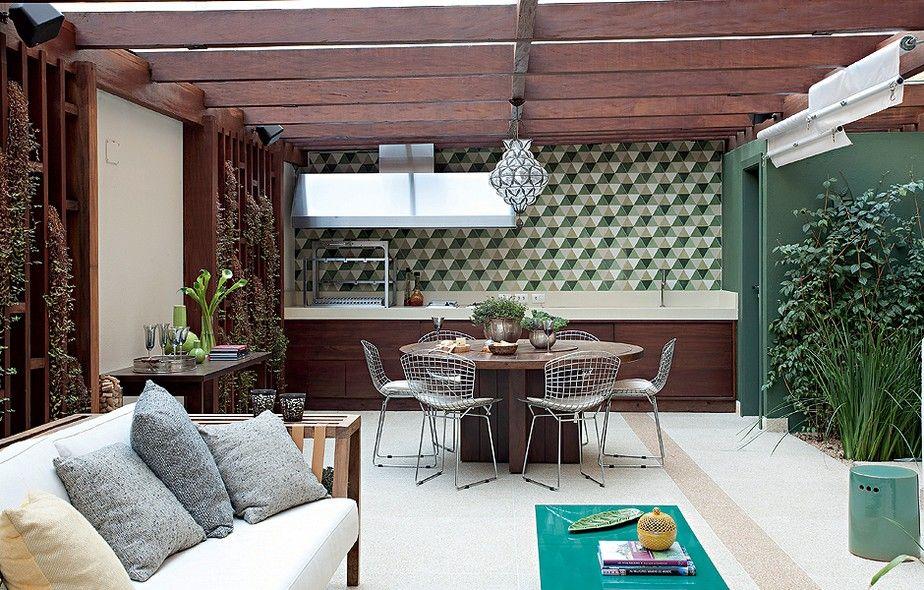 """O quintal de 120 m² tem área gourmet de 45 m². """"A ideia é ter um espaço para cozinhar sem abrir mão do verde"""", conta a arquiteta Flavia Gerab. O pergolado de cumaru faz sombra no cooktop e na churrasqueira e cria um ambiente agradável"""