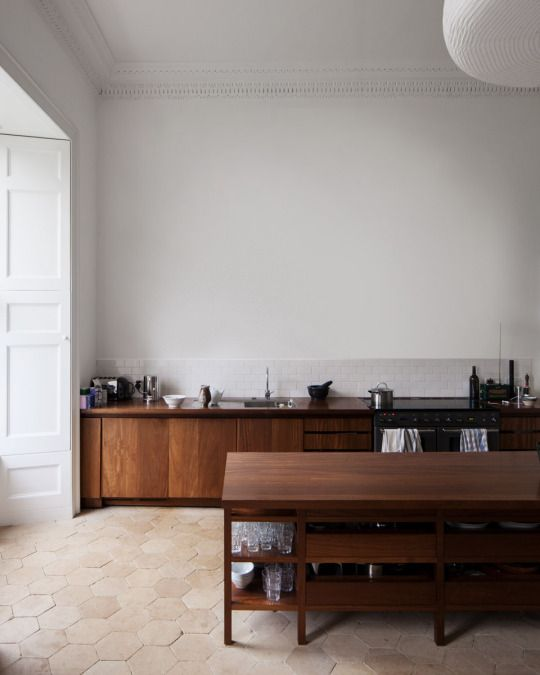 Minimal open airy neutral kitchen with grey-white walls and dark walnut cabinetry
