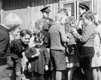 Kinder in einem Münchner Flüchtlingslager erhalten Spielsachen von Amerikanern, 1949.