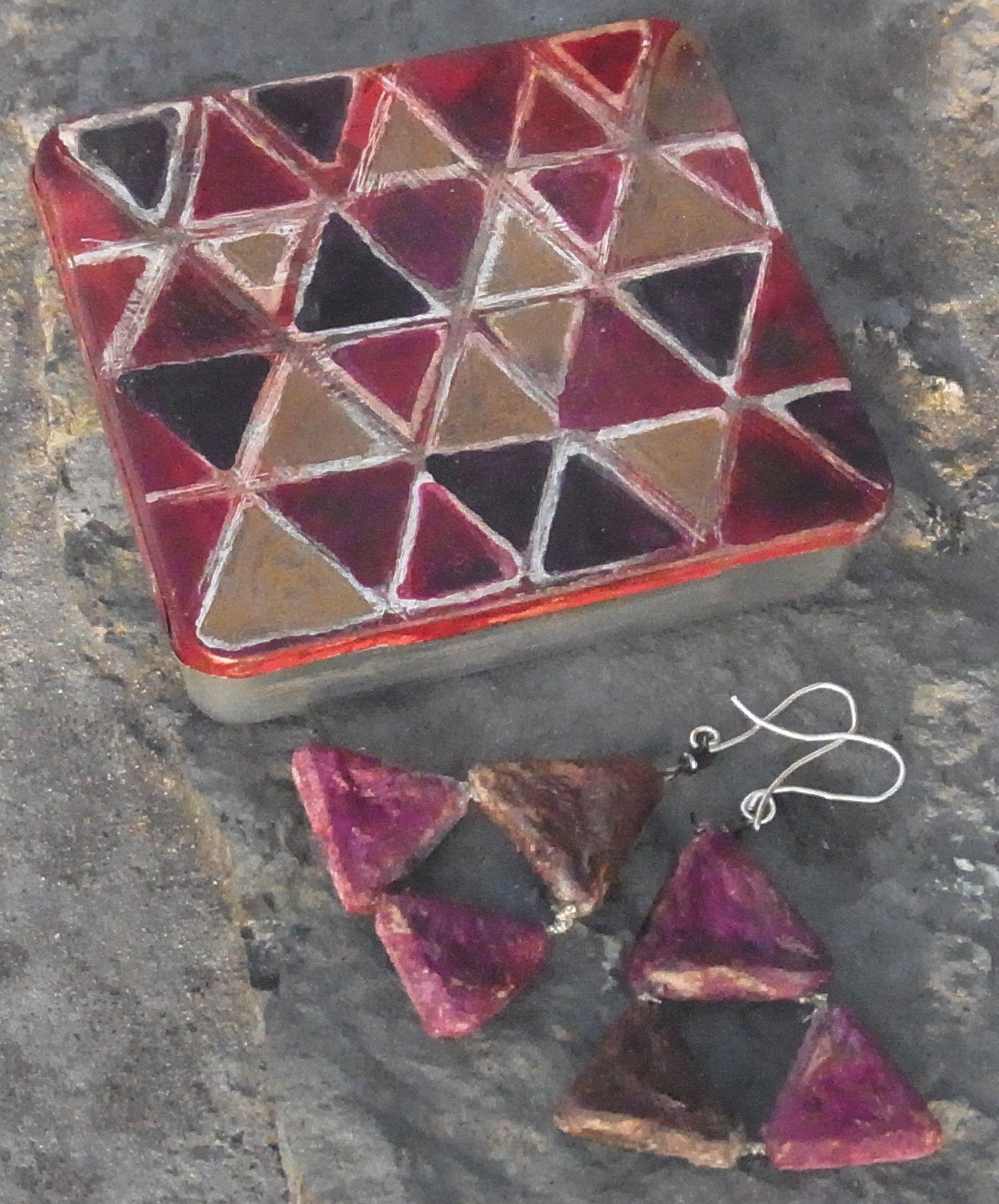 """Pendientes ultraligeros con tres triángulos, modelo """"canario"""" y lata pintada con los mismos motivos para guardarlos."""