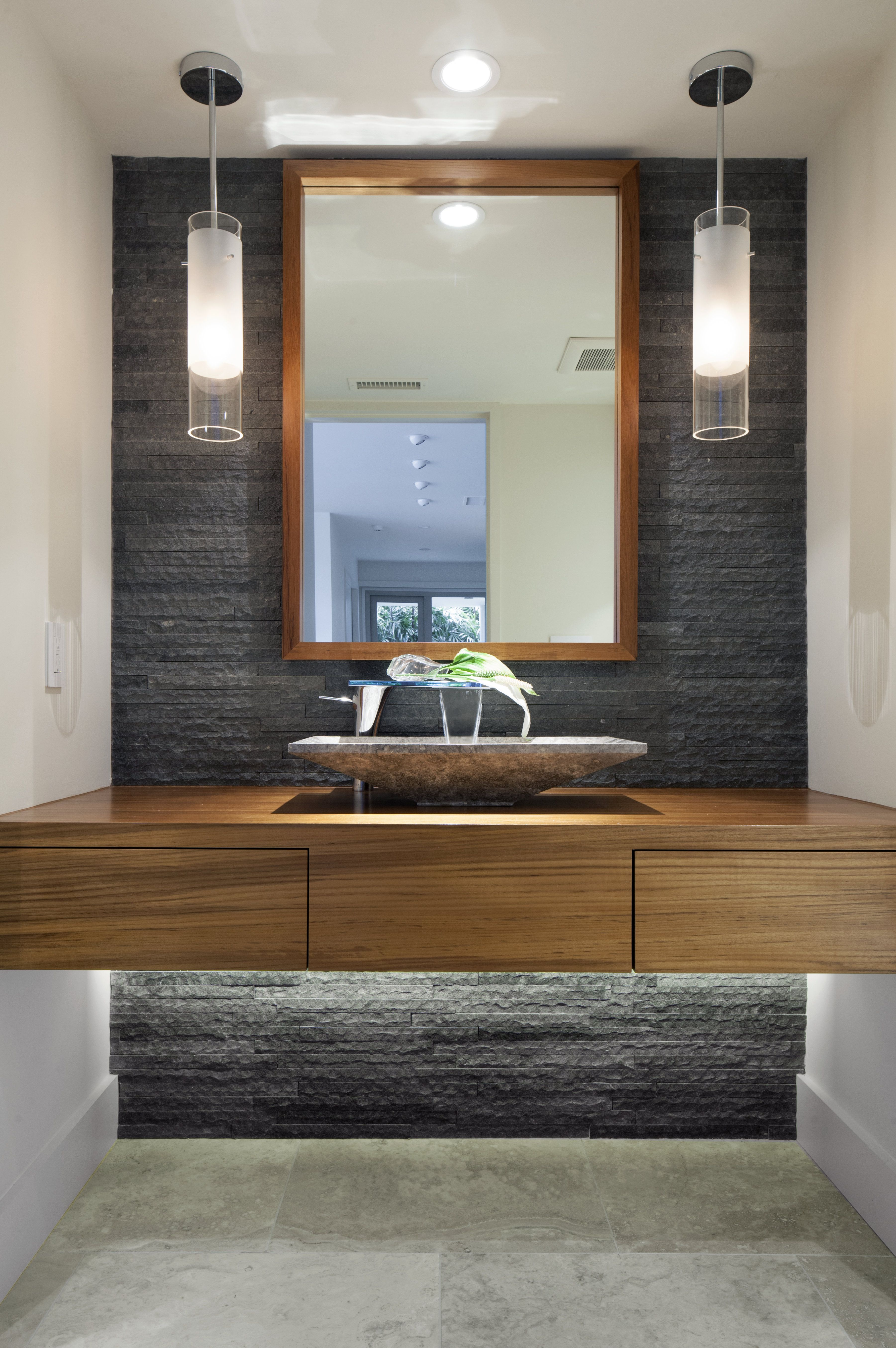 A modern bathroom with natural stone accent wall and pendant lights