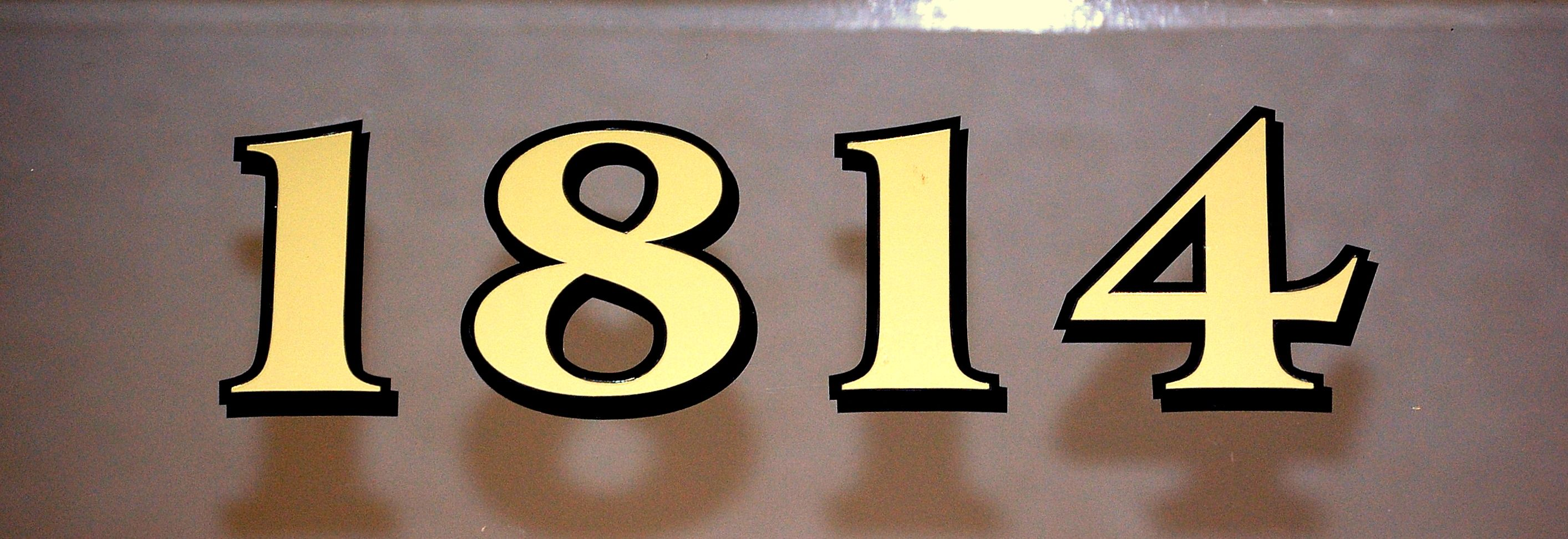 Traditional real gold house number for transom above entry door