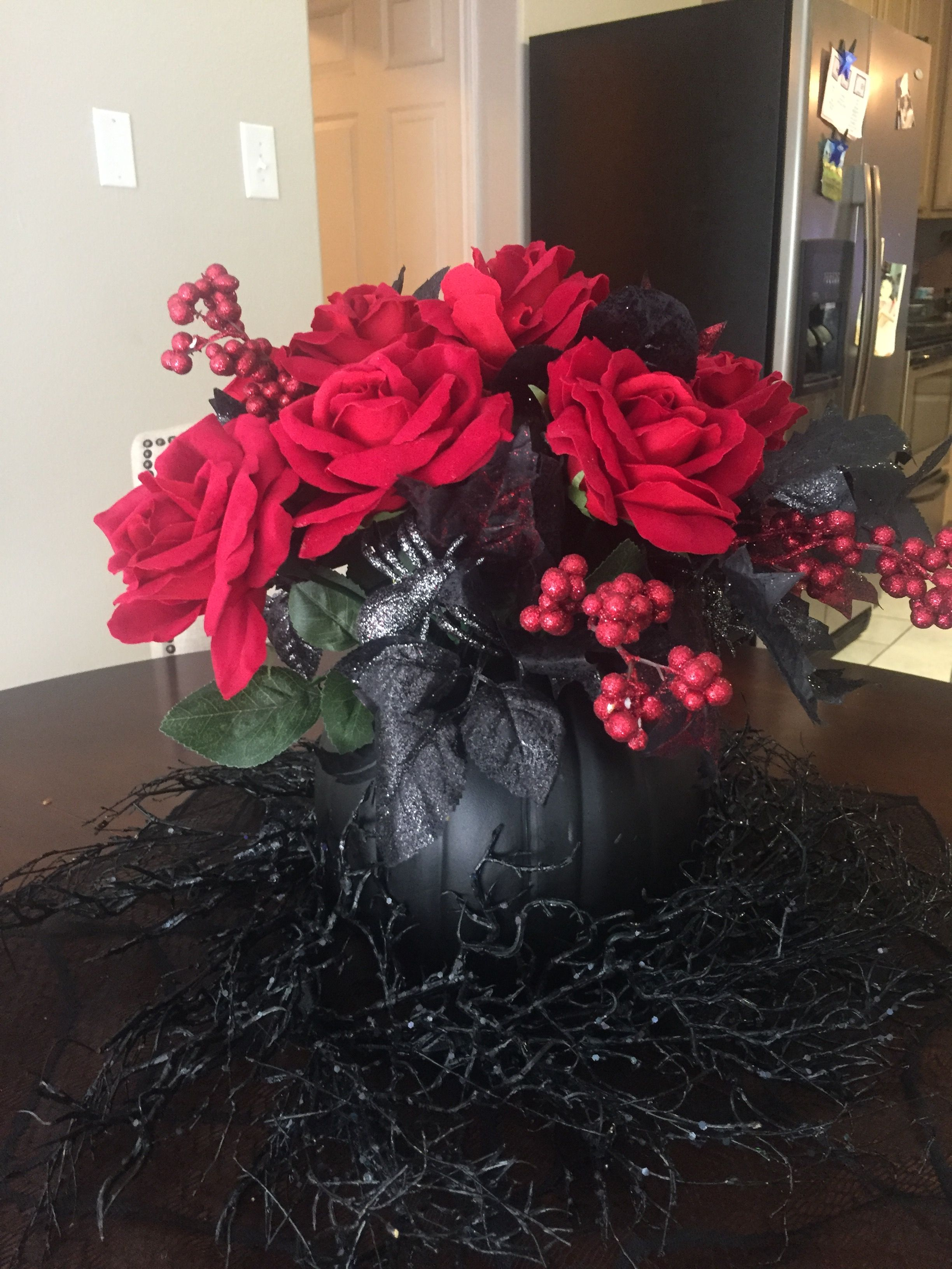 Halloween decor.  Black pumpkin, cut hole into pumpkin, added decorative black leaves with red berries, red roses, & a couple spiders to top off.